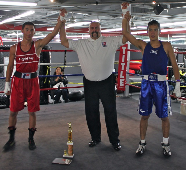 At the conclusion of Bout #25, referee Hondo Fontan holds up the arms of both Israel Mercado (L) of the Ultimate Warriors of Ontario, CA, the eventual winner, and Johnny Rivera of the San Diego Combat Academy to salute their efforts.