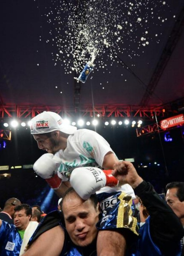 While enjoying his victory ride, Jhonny Gonzalez is shown ducking under a beer can thrown by an over zealous, fanatical Abner Mares fan. Photo: Harry How/Getty Images