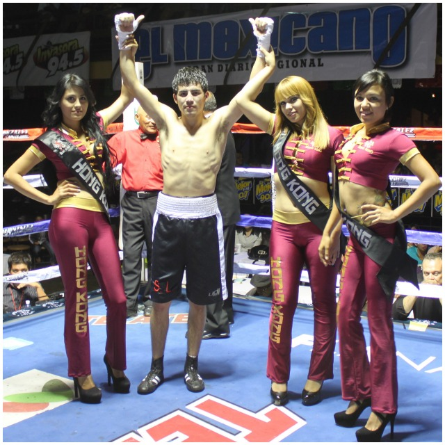 At the conclusion of his bout with Kiky Valenzuela, Jose Galvez has his arms raised in victory by the lovely ring card girls.