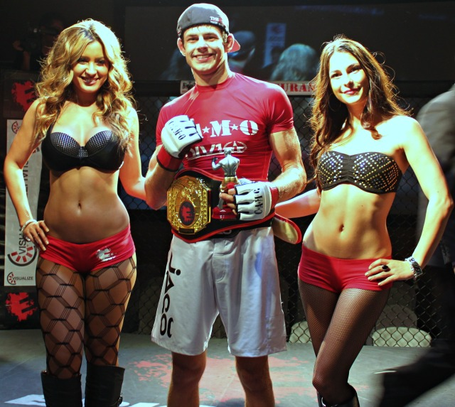 Tyler Sidders of The Arena MMA in Point Loma, along with two of the lovely Epic Fighting Ring Card Girls, poses for a photo after defeating the veteran Luther Smalls of Austin, Texas, to become the new Epic Fighting Lightweight Champion. Photo: Jim Wyatt