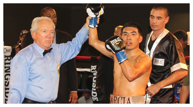 At the conclusion of the evening's Main Event at the Crowne Plaza Hanalei Hotel in Mission Valley, Aaron Garcia has his arm raised in victory after defeating KevinHoskins by TKO in the fifth round by referee Pat Russell. Alongside Garcia is his trainer Vince Parra.
