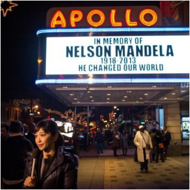A newscaster broadcasts the news of the passing of Nelson Mandela from under the marquee at the historic Apollo Theater in the Harlem neighborhood of Manhattan in New York City, on December 5, 2013. Photo: Andrew Burton/Getty Images