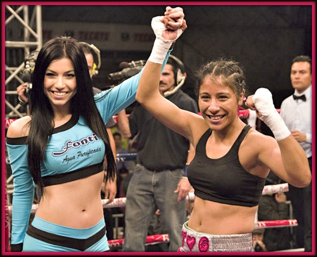 One of the show's hostesses raises Kenia Enriquez's arm in victory after she defeated Selene Lopez.