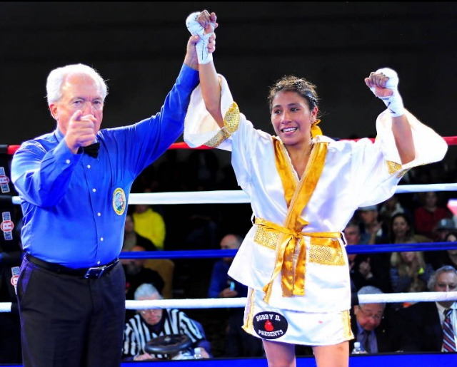 After her victory, Kenia Enriquez has her arm raised in victory by haall of Fame referee Pat Russell.