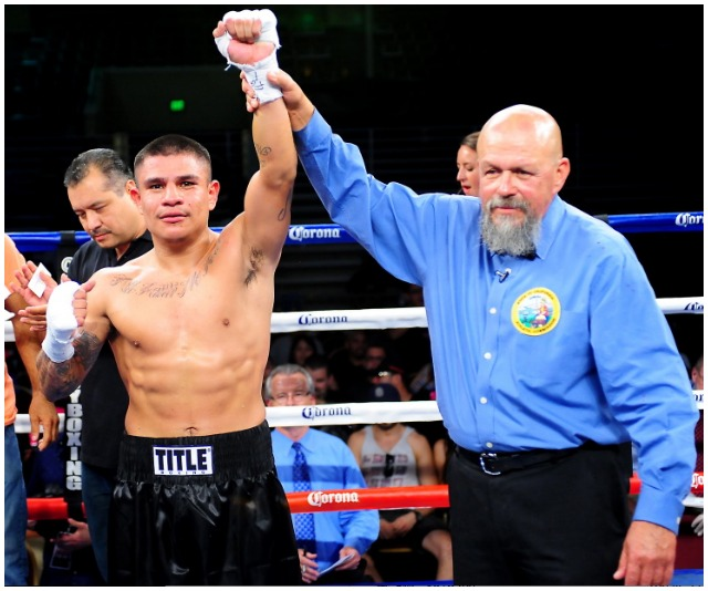 At the conclusion of Bout #6, the winner, Walter Santibanes has his arm raised in victory by referee Jose Cobian. Photo: Jim Wyatt