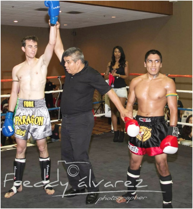 "At the conclusion of Bout #6, we see Eric Fore of Elite Muay Thai, San Luis Obispo, CA having his arm raised in victory by referee Vichai ""Rex"" Supkitpol after Fore scored a TKO victory over Charlie Morreo of Bob Chaney's Family Martial Arts, Murrieta, CA. Photo: Freddy Alvarez"