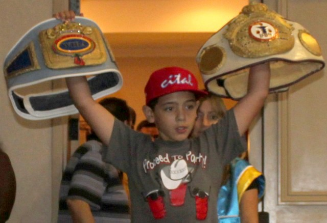 Youngster holds up the two championship belts won by Jolene Blackshear. Photo: Jim Wyatt