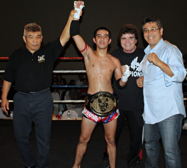 At the conclusion of Bout #4, the winner Ramon Gallardo has his arm raised by referee Vichai Supkitpol and is congratulated by the show's promoters Bob Chaney and Victor Beltran. congratulated by