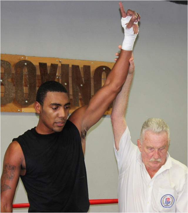 After the announcement of his unanimous decision win, referee Rick Ley raises the arm of the victorious Xavion Betts. Photos: Jim Wyatt