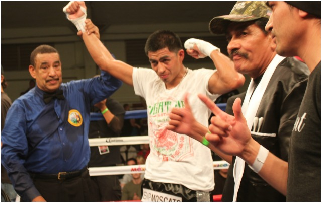 Proud father and proud brother Luis look on as Alan Sanchez has his arm raised in victory by referee Wayne Hedgepath. Photo: Jim Wyatt