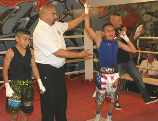 At the conclusion of Bout #4, Juan Medina III has his arm raised in victory after he defeated