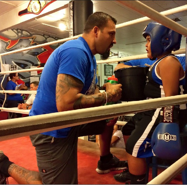 During a break between rounds, coach Juan Romo talks over strategy with his boxer Sergio Lopez.