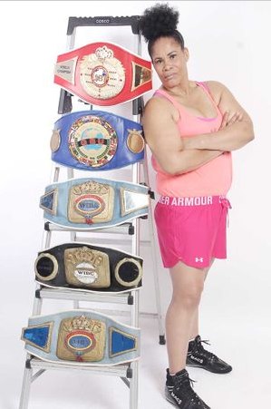 Heavyweight champion Gwendolyn ONeil poses for a photo with her many Championship belts.