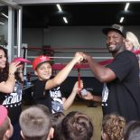 Julius Ballo, a USA Amateur Boxing sensation gets an assist from his coach Berlin Kerney IV while the many friends and family revel in the ribbon cutting ceremony. All photos: Jim Wyatt