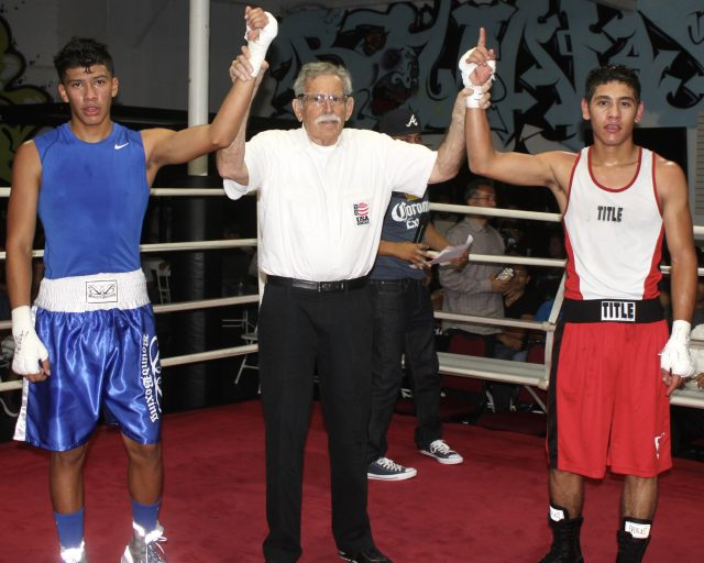 At the conclusion of Bout #10, we see referee Will White raising the arms of the combatants Ulises Bastididas (r) and Mario Ramos (l) of the Bound Boxing