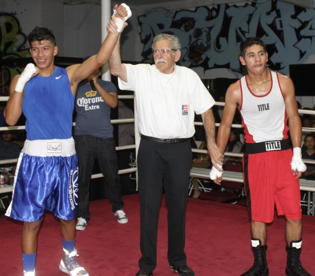 At the conclusion of Bout #10, Mario Ramos has his arm raised in victory