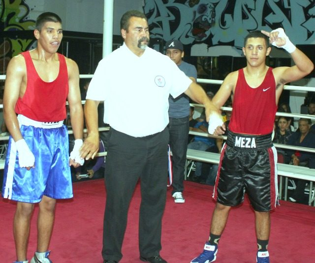 At the conclusion of Bout #6, Jason Meza of the Arena (r) has his arm raised in victory by referee Hondo Fontane.