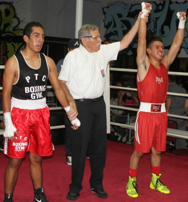 At the conclusion of Bout #11 we see referee Will White raising the arm of the victorious Leonardo Rosiles of Bound Boxing after he defeated Christian Martinez of the Pacific Training Center.