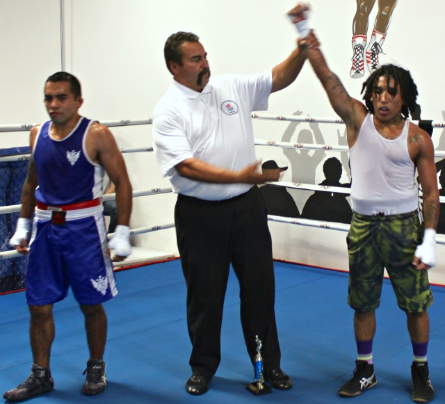 At the conclusion of Bout #7, it was John Ramirez (r) of the Wild Card Boxing Club having his arm raised in victory by refereeHondo Fontane.