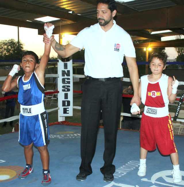 At the conclusion of Bout #12, the referee raises te arm of the victorious Esau Valerio.