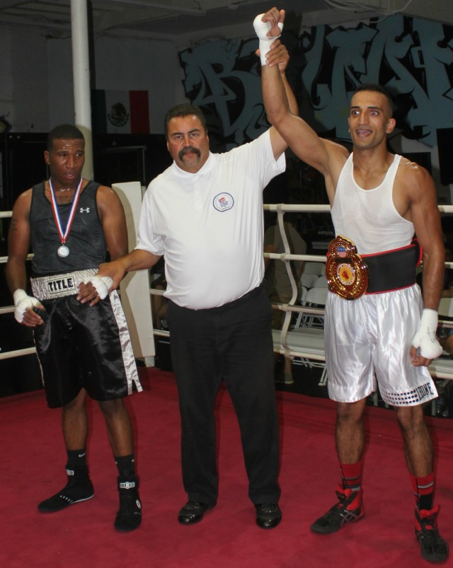 At the conclusion of Bout #6, we see referee Hondo Fontane raising the arm of the victorious Ali Ahmed of One Training Center, Spring Valley after his defeat of Joshua Harris of The Arena.