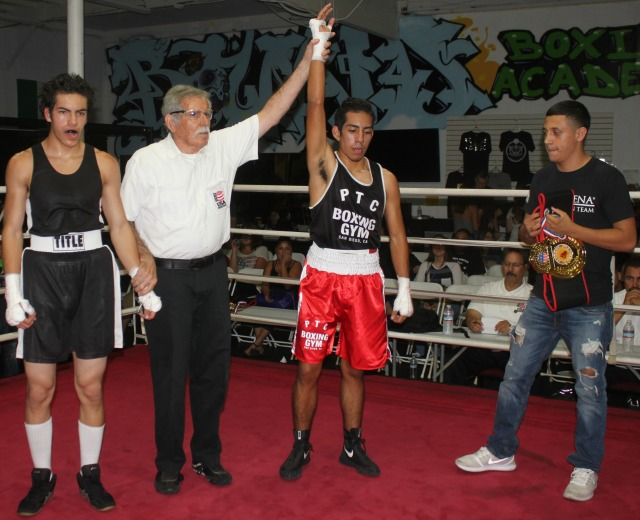 At the conclusion of Bout #5, we see referee Will White raising the arm of the victorious Christian Martinez, who like Tapia in Bout #4, is becoming better and better through listening to their coaches and doing the hard work in the gym.