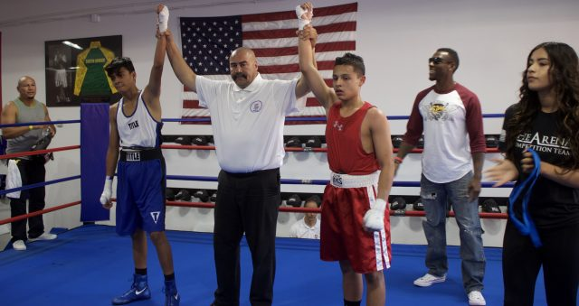 At the conclusion of their hard fought contest we see referee Hondo Fontane lifting the arms of