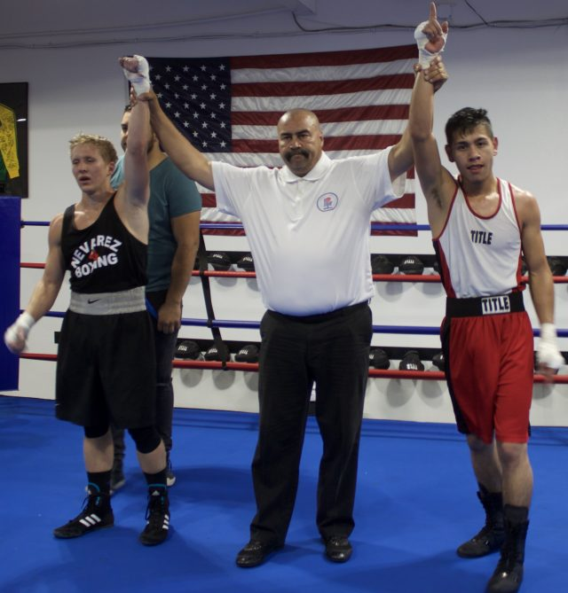 Showing his delight in their performance, referee Hondo Fontane, raises the arms of both combatants, Kyle Erwin (l) and Ulises Bastida (r).